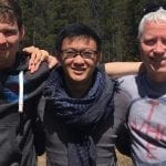 3 men smiling with a forest behind