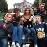 Five Students sitting on a car giving the peace sign