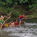 Children canoeing in the jungle