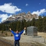 Jeff Yao standing in front of mountains with outstretched arms at Basecamp West