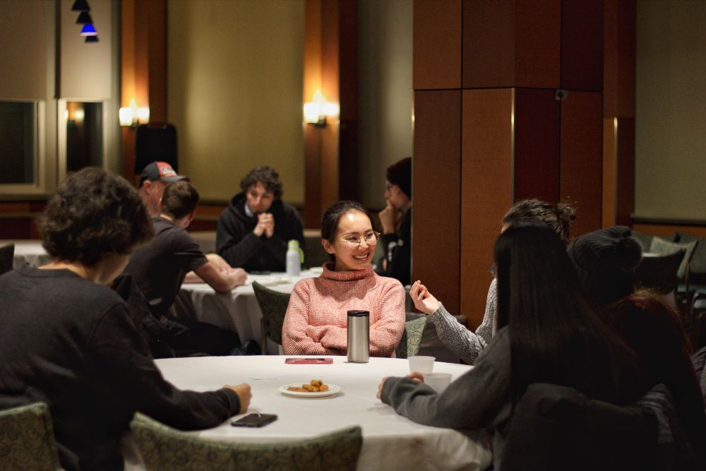 girl in pink sweater talking with others at a table